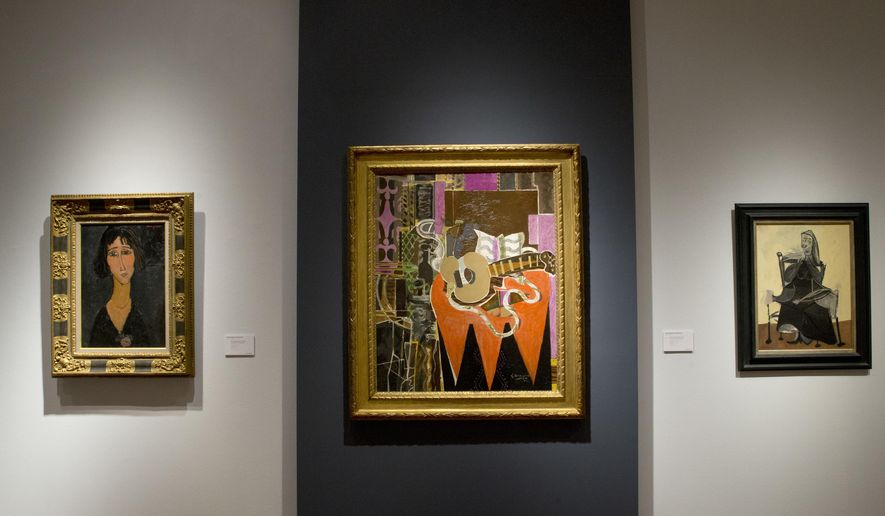 """In this Friday, April 29, 2016 photo, """"Mandolin with Partition (The Banjo),"""" center, by Georges Braque is on display next to 'Young Woman with a Rose,"""" right by Amedeo Modigliani, and """"Seated Woman"""" by Pablo Picasso during the press preview of """"Bound to Fail"""" at Christie's auction house in New York. (AP Photo/Mary Altaffer)"""