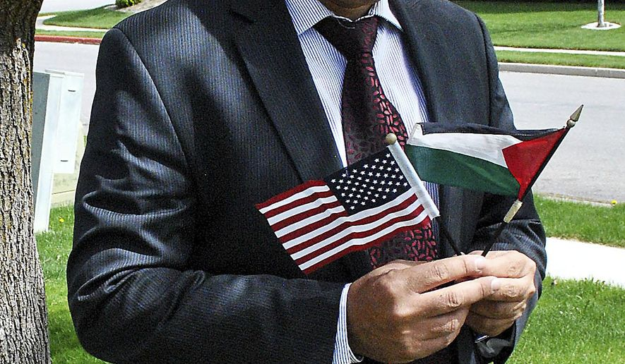 ADVANCE FOR WEEKEND EDITIONS - In this April 22, 2016 photo, former Logan Islamic Center president and co-founder of Cache Community Connections Said Ghabayen poses with an American and Palestinian flag outside his Logan home in Cache Valley, Utah. As a Ph.D. student in civil and environmental engineering at Utah State University in 2001, Palestinian native and Muslim Ghabayen became a local voice for peace following the Sept. 11, 2001 terrorist attacks. (Clayton Gefre/The Herald Journal via AP) MANDATORY CREDIT