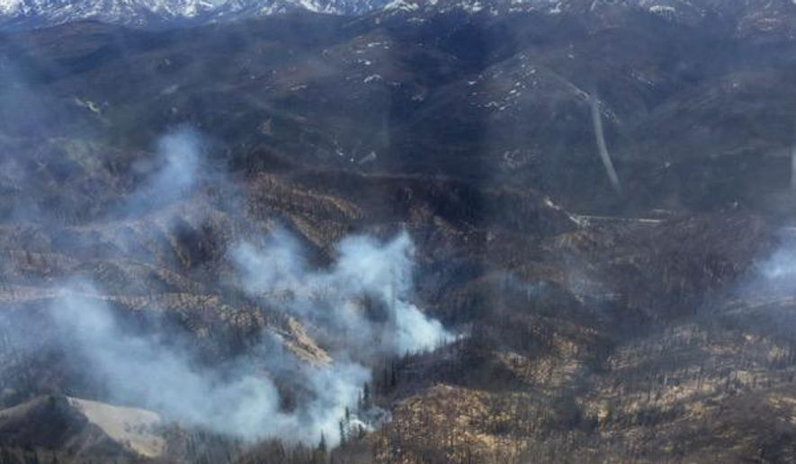 In this Wednesday, May 5, 2016 photo provided by the Alaska Division of Forestry, a wildfire believed to have started from underground coal seams burns near Healy, Alaska. Pockets of ignited coal smolder and burn in the area all year and last year ignited nine wildfires. The Alaska Division of Forestry used a helicopter to drop water on the fire to keep it contained within an old burn scar. (Cameron Winfrey/Alaska Division of Forestry via AP) MANDATORY CREDIT