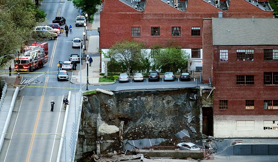Police officers and firefighters keep the Mulberry Street bridge clear of pedestrians after a retaining wall of the bridge collapsed in Harrisburg, Pa., Thursday, May 5, 2016. (Sean Simmers/PennLive.com via AP) MANDATORY CREDIT