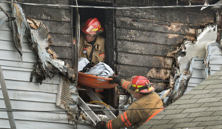 Syracuse firefighters remove a body through an upstairs window at the scene of a fatal fire Friday May 6, 2016 in Syracuse, N.Y. The blaze was reported early Friday morning.  When firefighters arrived just minutes after receiving a 911 call, the front of the house was engulfed in flames, officials said.   (David Lassman/The Syracuse Newspapers via AP) NO SALES; MANDATORY CREDIT