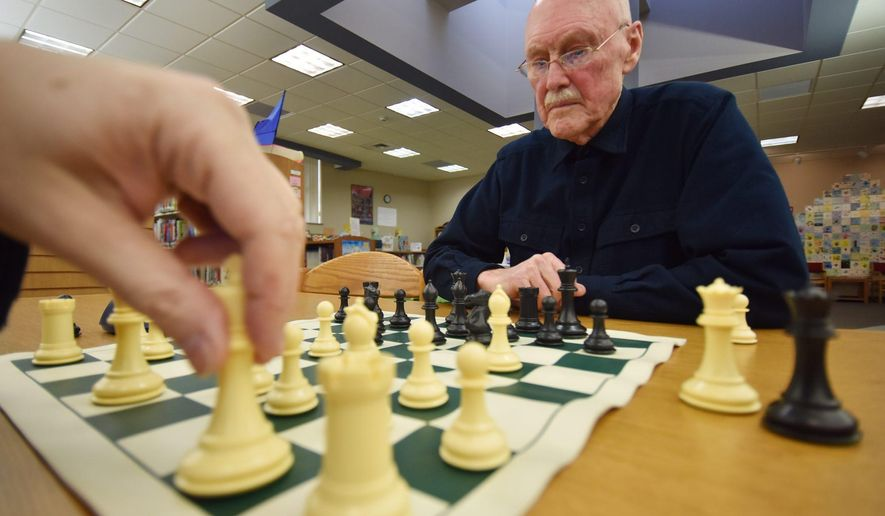 In this April 5, 2016 photo, Abington Chess Club member Paul Andrade, who has been a chess fan for decades, plays at the Abington Community Library, in Clarks Summit, Pa., against Greg Telepniovsky. (Jason Farmer/The Times & Tribune via AP) WILKES BARRE TIMES-LEADER OUT; MANDATORY CREDIT