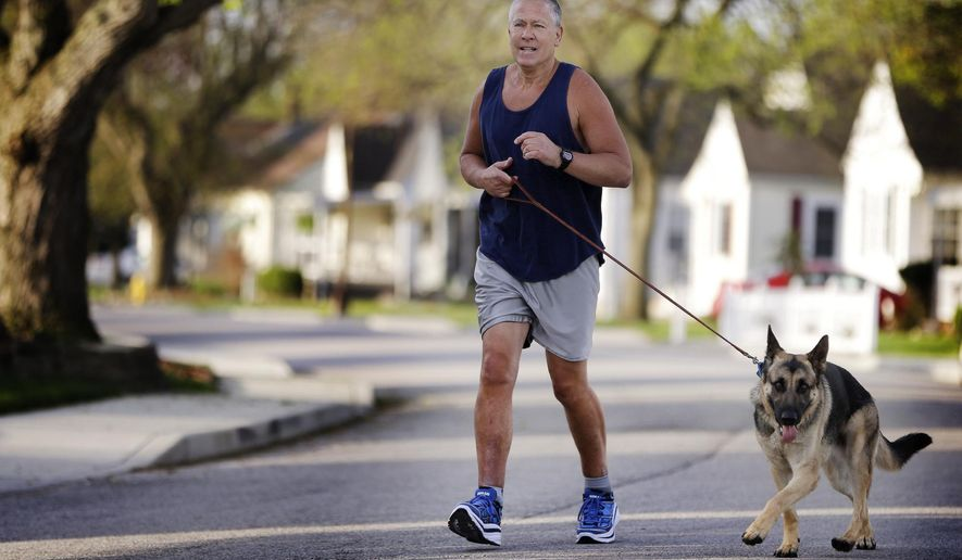 In this photo taken April 19, 2016, John Miller takes a run along the street of his Speedway, Ind., home, with is running partner and dog Zeke, a two-year-old German shepherd. Miller, who nearly lost his legs in an auto accident, uses mini-marathon as way to rebuild his life. (Mykal McEldowney/The Indianapolis Star via AP)  NO SALES; MANDATORY CREDIT