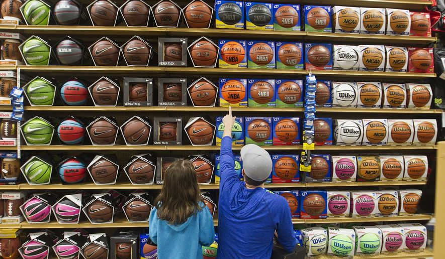 ADVANCED FOR RELEASE SUNDAY, MAY 8, 2016 Rod Call and his daughter Savannah Call, 5, pick out basketballs while shopping on April 1, 2016 in Traverse City, Mich, for basketball gear for children in his Milk Crate Basketball project, which helps disadvantaged youth with obtaining equipment to play the game. (Jan-Michael Stump/Traverse City Record-Eagle via AP)