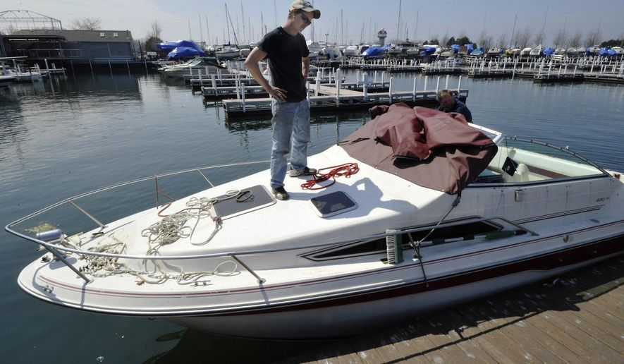 "In this April 22, 2016 photo, Bay Harbor Marina service technician Neal Rudler helps get ""One More Toy"" in the water in Erie, Pa. (Greg Wohlford /Erie Times-News via AP)  MANDATORY CREDIT; MAGS OUT"