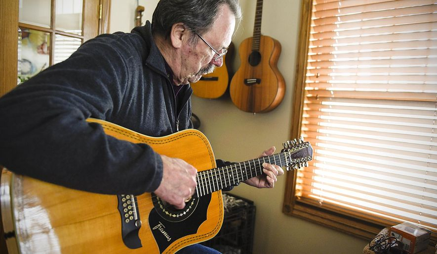 """ADVANCE FOR WEEKEND EDITIONS MAY 7-8 - In this April 5, 2016 photo, Al Hams, 72, plays one of his guitars at his home in Sauk Rapids. Minn. Al Hams is 72. He has Parkinson's disease, very likely due to his exposure to the chemical defoliant Agent Orange during the year he served with the U.S. Army in Vietnam. He calls that the """"missing year""""  a period Hams tried to forget. (Jason Wachter/St. Cloud Times via AP)  NO SALES; MANDATORY CREDIT"""