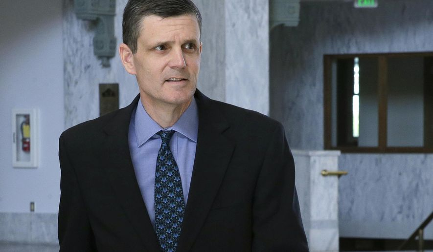 FILE - In this April 26, 2016 file photo, Washington State Auditor Troy Kelley leaves the federal courthouse in Tacoma, Wash. Kelley has cut three staffers since his federal fraud trial ended with a jury deadlocked on most of the counts against him. Reasons for the firings were not clear. (AP Photo/Ted S. Warren, File)