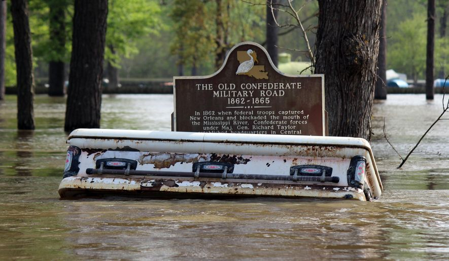 In a Wednesday, March 16, 2016 photo, caskets float away from a nearby cemetery during flooding from heavy rains in Calcasieu Parish, La. The parish Coroner's Office earlier this month completed the recovery of caskets and vaults or lids that floated from their resting places during flooding March 12 and beyond. Officials said 85 caskets were recovered, most from Niblett's Bluff Cemetery in Vinton. The recovered remains have been placed in refrigerated trucks parked at the coroner's office as investigators begin the identification and re-interment process. (Emily Dalfrey via AP)