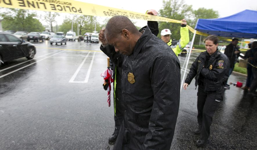 Assistant Montgomery County, Md. Police Chief Darryl McSwain leaves after speaking to reporters under a tent during a heavy rain outside Westfield Montgomery Mall in Bethesda, Md., after a shooting Friday, May 6, 2016.  Police say three people were hurt in the shooting. (AP Photo/Jose Luis Magana)