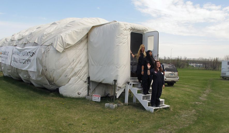 University of North Dakota graduate students, from top, Carolyn Newton, Poonam Josan and Brittany Zimmerman, emerge from the school's inflatable mars habitat on Friday, May 6, 2016, in Grand Forks, N.D., after a 10-day mission. The space studies students performed a variety of experiments mainly related to how isolation affects crew cohesion. (AP Photo/Dave Kolpack)