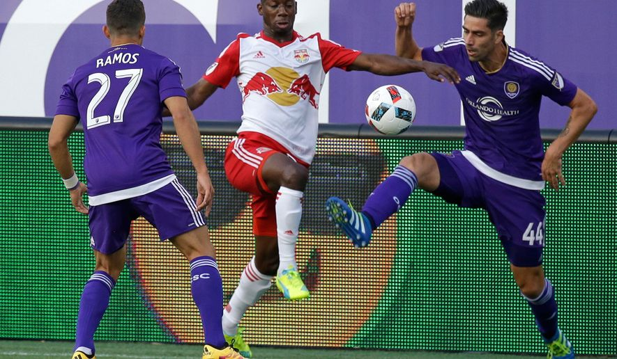 New York Red Bulls' Bradley Wright-Phillips, center, moves the ball between Orlando City's Sebastian Hines (3) and David Mateos (44) during the first half of an MLS soccer game, Friday, May 6, 2016, in Orlando, Fla. (AP Photo/John Raoux)