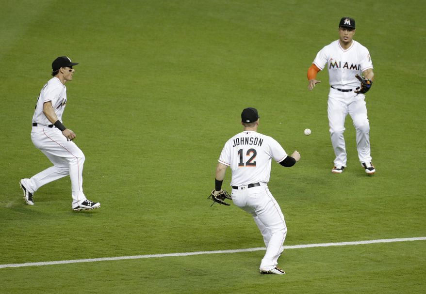 Miami Marlins second baseman Derek Dietrich, left, first baseman Chris Johnson (12), and right fielder Giancarlo Stanton, right, can't get to a ball hit by Philadelphia Phillies' Maikel Franco during the third inning of a baseball game, Friday, May 6, 2016, in Miami. (AP Photo/Lynne Sladky)