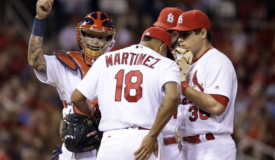 St. Louis Cardinals' Yadier Molina, left, calls for a trainer as he stands on the mound with starting pitcher Carlos Martinez, center, and Aledmys Diaz during the fourth inning of a baseball game against the Pittsburgh Pirates Friday, May 6, 2016, in St. Louis. Martinez left the game. (AP Photo/Jeff Roberson)