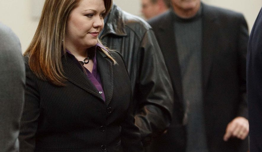 In this photo taken Nov. 3, 2009, Elissa Wall, front, with her husband Lamont Barlow, immediately behind her, stand during her lawsuit against polygamous leader Warren Jeffs at Utah Supreme Court in Salt Lake City. Wall, who says Jeffs forced her to marry her cousin when she was 14, has settled her lawsuit against the group's communal property trust for $2.75 million, her lawyer said Friday, May 6, 2016. (Trent Nelson/The Salt Lake Tribune via AP) DESERET NEWS OUT; LOCAL TELEVISION OUT; MAGS OUT; MANDATORY CREDIT