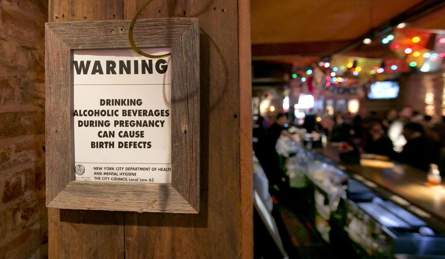 The drinking and pregnancy warning notice is posted behind the bar at the Mad Dog & Beans Mexican Cantina, in New York's Financial District, Friday, May 6, 2016. Pregnant women can't be barred from New York City bars or refused alcoholic drinks just because they're expecting, under new official guidance on a city rights law. Human Rights Commission officials say they're not saying that expectant mothers should drink, but that such health decisions are up to the woman, not a bartender. (AP Photo/Richard Drew)
