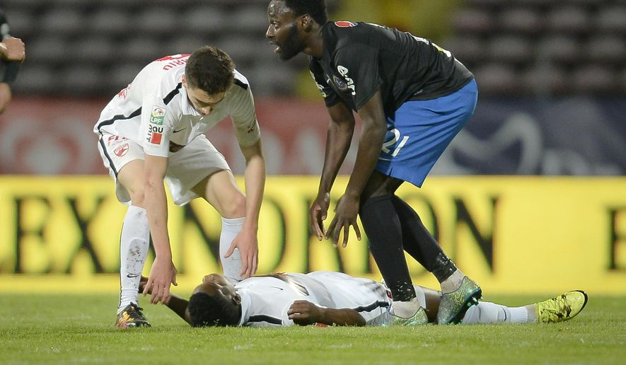 Dinamo's Patrick Ekeng of Cameroon lies on the pitch after collapsing during a league game in Bucharest, Romania, Friday, May 6, 2016. Dinamo Bucharest player Patrick Ekeng died after he collapsed during a match in the Romanian capital on Friday, doctors said. He was 26. (AP Photo) ROMANIA OUT