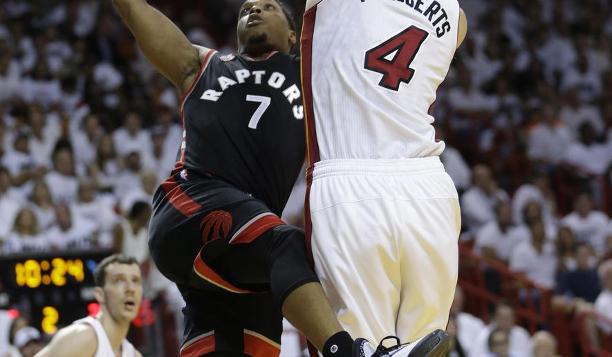 Toronto Raptors guard Kyle Lowry (7) attempts a shot to the basket as Miami Heat forward Josh McRoberts (4) defends, during the first half of Game 3 of an NBA second-round playoff basketball series Saturday, May 7, 2016, in Miami. (AP Photo/Alan Diaz)