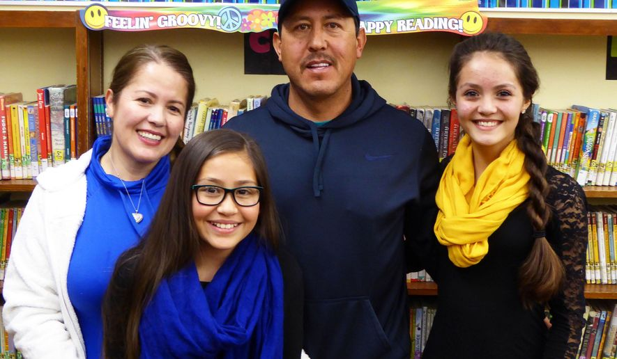 ADVANCE FOR SATURDAY MAY 7 -  From left in this Friday, April 15, 2016, photograph, Rosina, Diana, Rogelio and Maylyn Arellano are shown in the library in Sandrock Elementary School in Craig, Colo. The Arellanos' two daughters, as well as their two sons, were able to learn English as well as Spanish at home but now a new challenge has emerged: keeping the proficiency of bilingualism alive as well as the presence of their Mexican culture as they thrive in a Colorado community where mostly English is spoken. (Michael Neary/Craig Daily Press via AP)