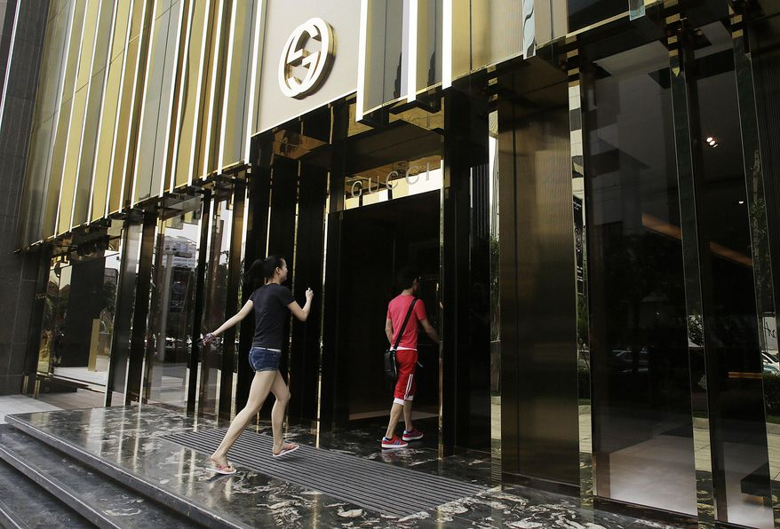 """FILE - In this June 13, 2012 file photo, people walk in a Gucci brand shop in Shanghai, China. Gucci America has quit the International Anti-Counterfeiting Coalition, the second defection since the Washington, D.C.-based group allowed Chinese e-commerce giant Alibaba to become a member in April. Michael Kors walked out of the IACC last month, calling Alibaba """"our most dangerous and damaging adversary."""" The outrage over Alibaba's membership raises fresh questions about how effective Alibaba has been in fighting fakes as it pushes to take its e-commerce juggernaut global. (AP Photo/Eugene Hoshiko, File)"""