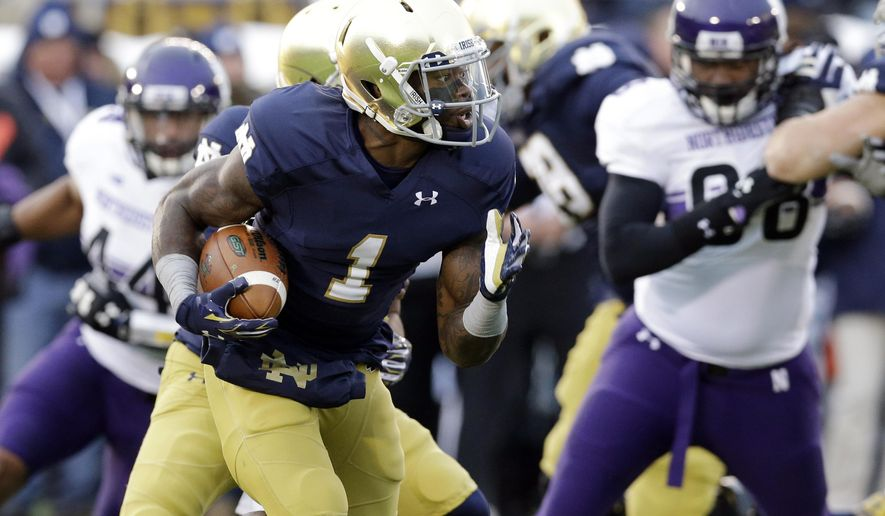 """CORRECTS THAT SCHOOL SAYS BRYANT IS ALIVE, AFTER ISSUING STATEMENTS THE HE DIED - FILE - In this Nov. 15, 2014, file photo, Notre Dame running back Greg Bryant (1) runs with the ball against Northwestern during the first half of an NCAA college football game in South Bend, Ind. UAB coach Bill Clark said Saturday, May 7, 2016, that Bryant is """"still fighting for his life"""" after he was shot in South Florida. UAB had issued statements earlier in the day before from Clark, President Ray Watt and athletic director Mark Ingram saying that Bryant had died. Bryant, a former Notre Dame player, was the biggest name in UAB's first recruiting class since restarting the football program.  (AP Photo/Nam Y. Huh, File)"""