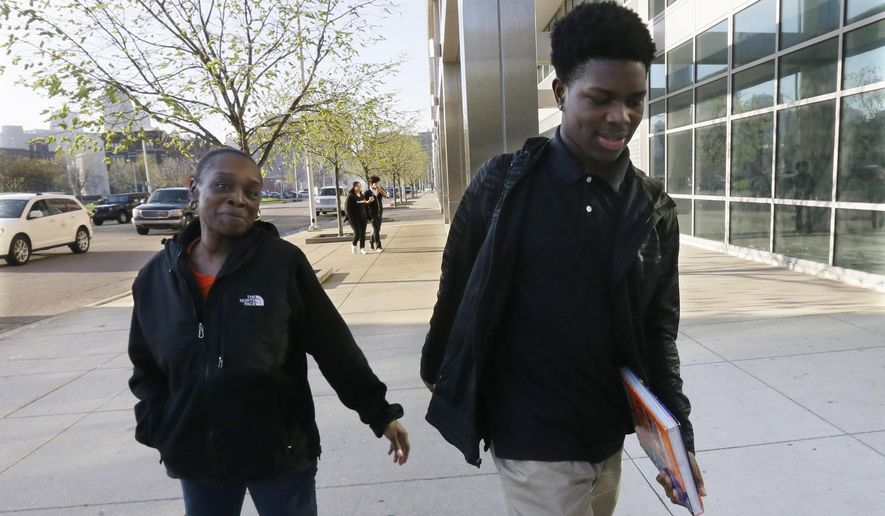 In a photo from Thursday, May 5, 2016, Tomi Sawyers, left, drops her son Anthony Sawyers off at the Cass Technical High School in Detroit. Anthony Sawyers is a sophomore at Detroit's pre-eminent public high school, Cass Tech, where textbooks aren't allowed out of his classrooms _ even to take home to study. That, his mother Tomi says, is a sign of how dire financial troubles are in the district, which other parents and educators say has had chronic shortages of books, paper and other supplies. (AP Photo/Carlos Osorio)