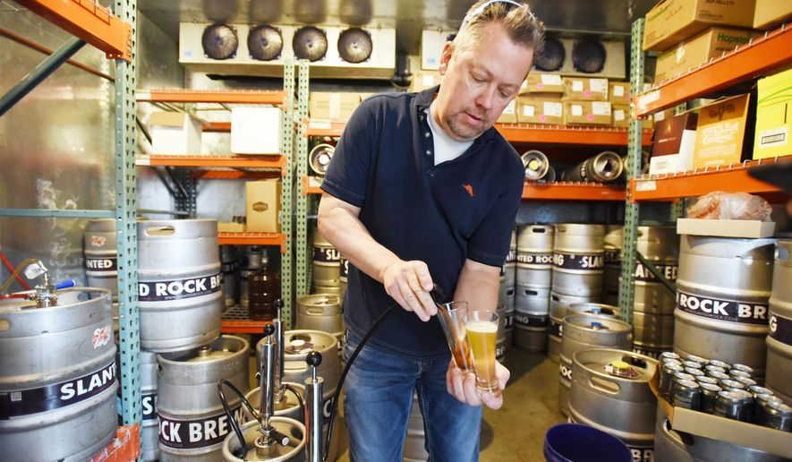 ADVANCE FOR USE SATURDAY,  MAY 7 - In this photo taken April 20, 2016, Bob Lonseth, brewmaster and CEO of Slanted Rock Brewing, pours a couple samples of the test batches of beer that he made at the Meridian, Idaho brewery using dried fruit powders produced at Nampa's Milne Fruit Products. (Greg Kreller/The Idaho Press-Tribune via AP)  MANDATORY CREDIT