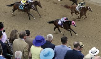 Fans watch race five before the 142nd running of the Kentucky Derby horse race at Churchill Downs Saturday, May 7, 2016, in Louisville, Ky. (AP Photo/Charlie Riedel)