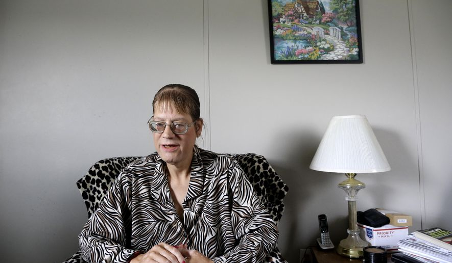 In this Wednesday, May 4, 2016 photo Angela Bridgman, a transgender woman, is shown at her home in Wendell, N.C. Bridgman, 44, moved her small medical billing and transcription business to North Carolina in 2014. But since the passage of the North Carolina HB2 law, she has taken to carrying her birth certificate that reflects her female gender. (AP Photo/Gerry Broome)