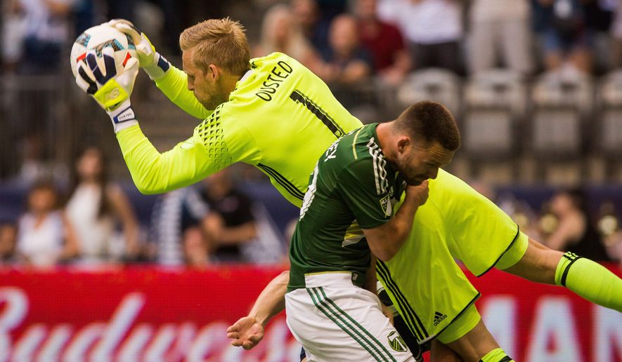 Vancouver Whitecaps goalkeeper David Ousted, left, makes a save as Portland Timbers' Jack McInerney (99) makes contact during the second half of an MLS soccer game in Vancouver, British Columbia, Saturday, May 7, 2016. (Ben Nelms/The Canadian Press via AP) MANDATORY CREDIT
