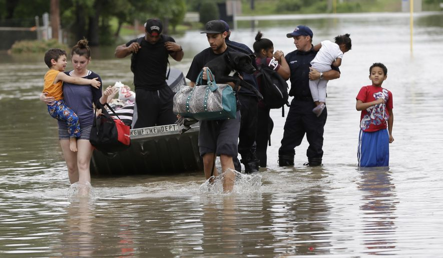 FILE - In this April 19, 2016 file photo, residents walk through floodwaters after being evacuated from their flooded apartment complex, in Houston. It's believed the El Nino warm waters in the Pacific have been responsible for above-average rainfall over much of Texas and the Southwest the past year. (AP Photo/David J. Phillip, File)
