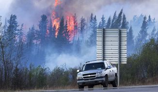 Flames flare up from hotspots along a highway to Fort McMurray, Canada, Sunday, May 8, 2016. (Ryan Remiorz/The Canadian Press via AP) MANDATORY CREDIT