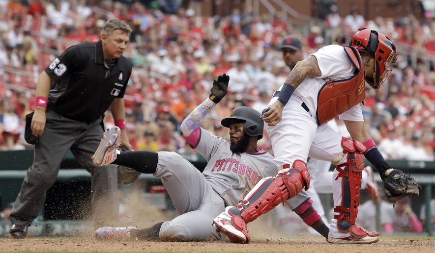 Pittsburgh Pirates' Josh Harrison, center, scores past St. Louis Cardinals catcher Yadier Molina, right, and home plate umpire Greg Gibson, left, during the ninth inning of a baseball game Sunday, May 8, 2016, in St. Louis. (AP Photo/Jeff Roberson)