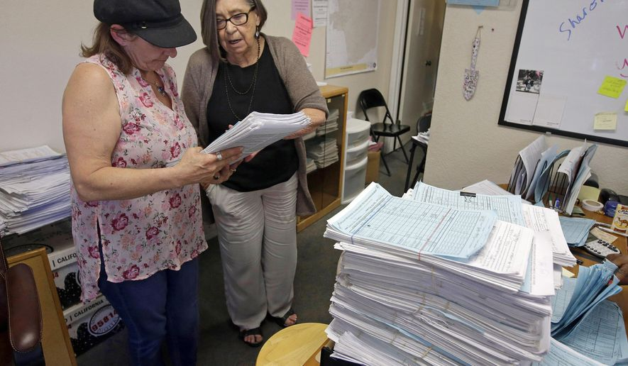 In this April 20, 2016, photo, Eileen Ray, right, president of Discovery Petition Management reviews petition signatures with Teresa Torkelson in Sacramento, Calif. Discovery Petition is one of several companies that is having a banner year in California, a hotbed for voter initiatives. (AP Photo/Rich Pedroncelli)