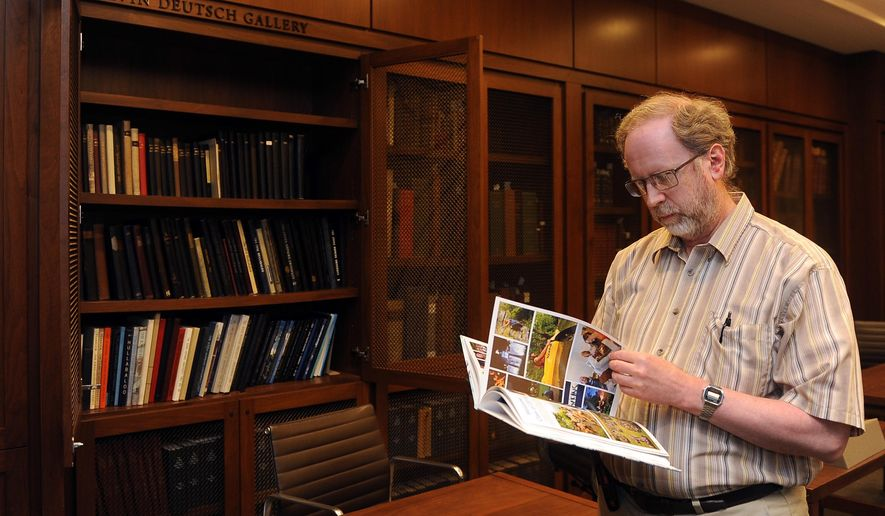 James Stimpert, senior reference archivist at the Johns Hopkins University Sheridan Libraries, looks at a copy of one of the university's yearbooks, April 22, 2016. The last one was published in 2015, and they will no longer be published. (Barbara Haddock Taylor/Baltimore Sun Media Group via AP)