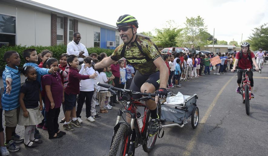In this April 22, 2016 photo, volunteer Dave Perreault high fives students during a book delivery by Ride for Reading to students at Haywood Elementary School in Nashville, Tenn. Ride for Reading puts books in the hands of low-income children via bicycle, promoting literacy and healthy living. (Samuel M. Simpkins/The Tennessean via AP) NO SALES; MANDATORY CREDIT