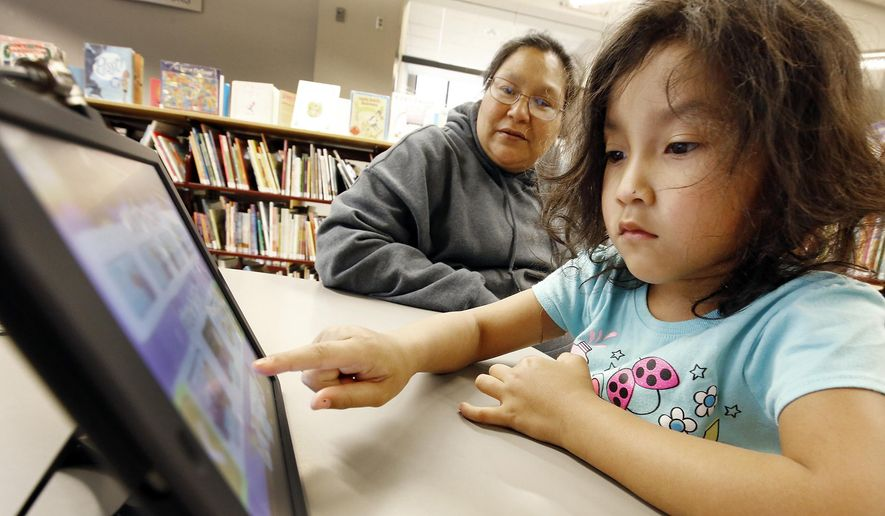 Kerri Zaleta, Sioux City, looks on as her daughter Alivia Fernandez, 5, uses an iPad at the Sioux City Public Library in Sioux City, Iowa, Wednesday, April 27, 2016. In a world where smartphones, iPads, Kindles and Netflix constantly compete for people's attention, Sioux City Public Library Director Betsy Thompson acknowledges fewer people are walking into the library to check out a book. Over the past five years, overall checkouts have dropped nearly 23 percent. (Jim Lee/Sioux City Journal via AP) MANDATORY CREDIT