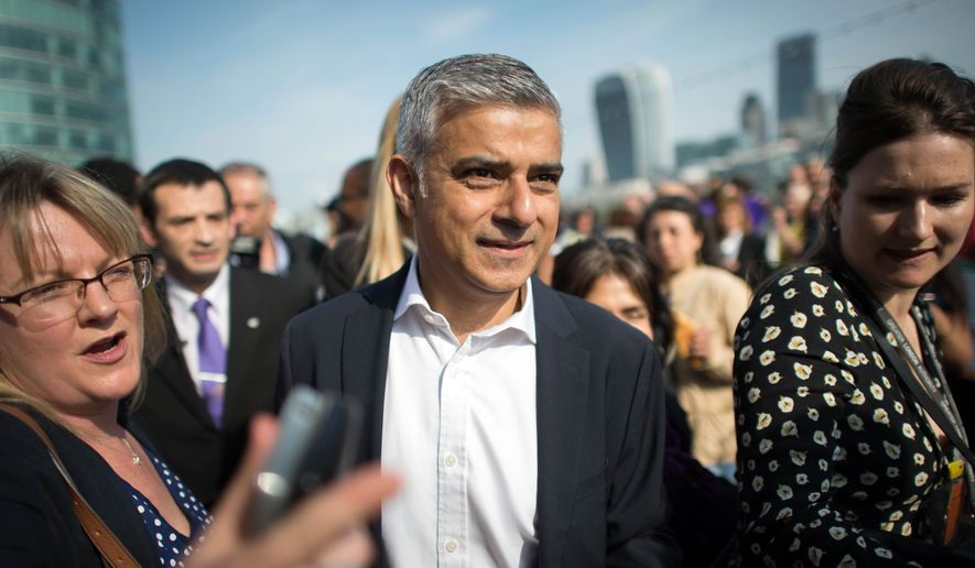 In this file photo from May 9, 2016, newly elected London's mayor Sadiq Khan, center, is greeted by well wishers outside City Hall in London, on his first day as mayor. Jonathan Brady/PA via AP) UNITED KINGDOM OUT NO SALES NO ARCHIVE **FILE**