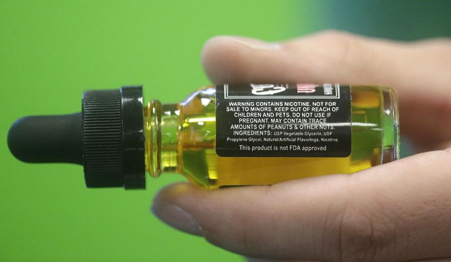 FILE - This Aug. 14, 2014, file photo shows a child-proof refill bottle of liquid nicotine in Salt Lake City. Electronic cigarettes have sickened rising numbers of young children, a study of U.S. poison center calls has found. Most cases involve swallowing liquid nicotine. (AP Photo/Rick Bowmer, File)