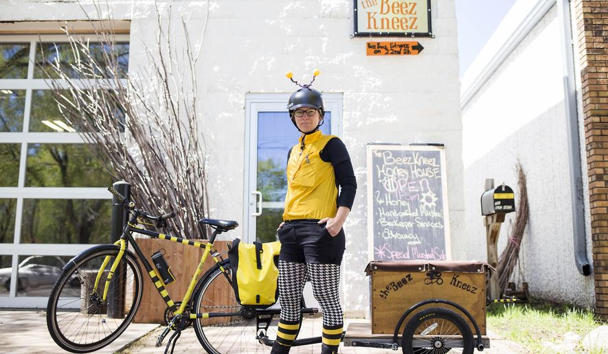 In a Friday April 29, 2016 photo, founder and beekeeper Kristy Lynn Allen poses for a portrait outside of The Beez Kneez in Minneapolis. In addition to the LLC's efforts to educate the public about beekeeping in the Twin Cities, Allen delivers both honey and live bees throughout the community via her bicycle. (Liam James Doyle\The Minnesota Daily via AP)