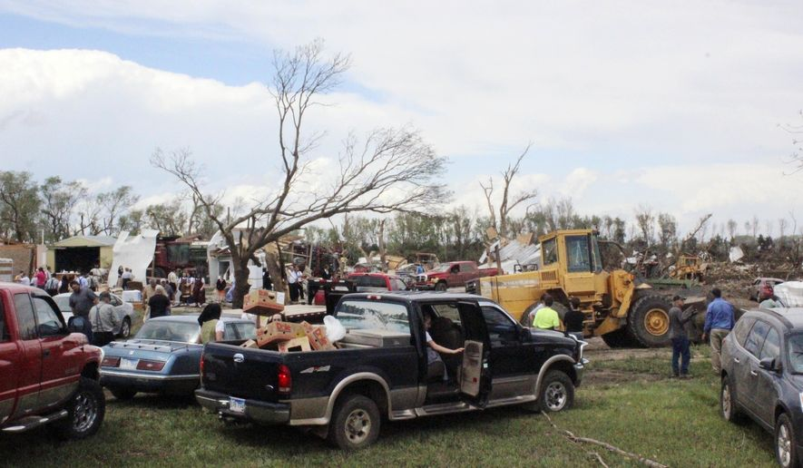 FILE - In this May 10, 2015, photo, dozens of people gather to help with cleanup efforts at a farm that was severely damaged by a tornado in Delmont, S.D. Delmont residents are recounting harrowing tales of survival on the one-year anniversary of the Mother's Day 2015 tornado that devastated the small community. (AP Photo/Regina Garcia Cano, File)