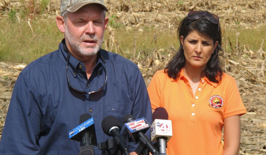 FILE - In this Aug.19, 2013 file photo, farmer John Pendarvis, with South Carolina Gov. Nilkki Haley looking on, discusses the effect of the heavy rains on farming during a news conference at his farm outside Harleyville, S.C. Gov. Nikki Haley has said, Monday, May 9, 2016, that she will veto a bill that would give $40 million in aid to farmers devastated by October's historic floods because it is help not offered to any other small businesses. Pendarvis said government treats groups different all of the time and this was an unprecedented disaster. (AP Photo/Bruce Smith, File)