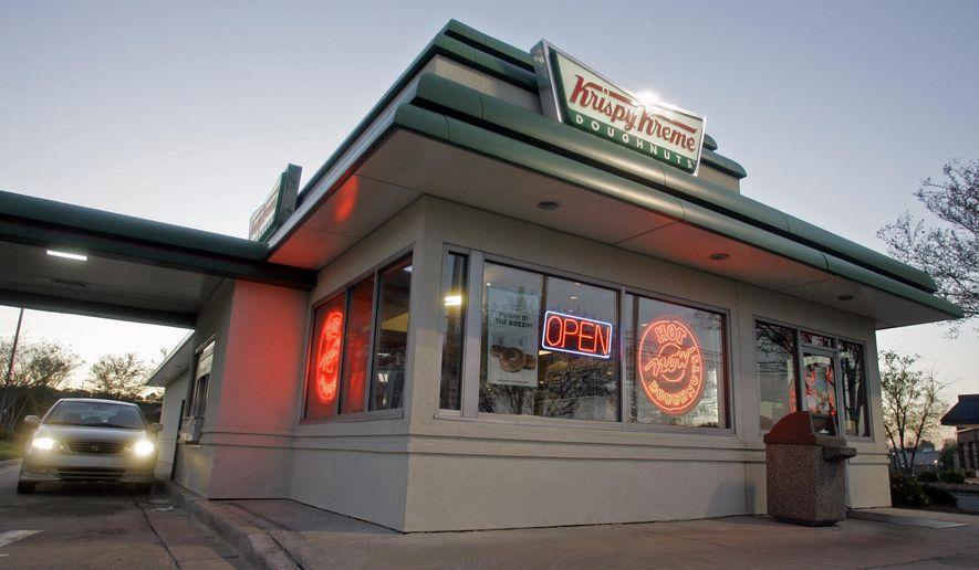 In this April 17, 2008, file photo, a customer picks up doughnuts at the drive through at a Krispy Kreme store in Matthews, N.C. (AP Photo/Chuck Burton, File)