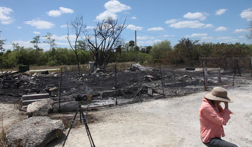 In a Sunday, April 10, 2016 photo, Niki Butcher takes a break while photographing the aftermath of a fire that destroyed Monroe Station in Ochopee, Fla., on Satruday night Officials on Monday, May 9 say a photo shoot sparked a fire that destroyed the historical landmark along the Tamiami Trail through Florida's Everglades. Monroe Station was on the U.S. National Register of Historic Places and was originally constructed in the 1920s.  (Jack Hardman/The News-Press via AP)  MAGS OUT; NAPLES OUT;  NO SALES; MANDATORY CREDIT