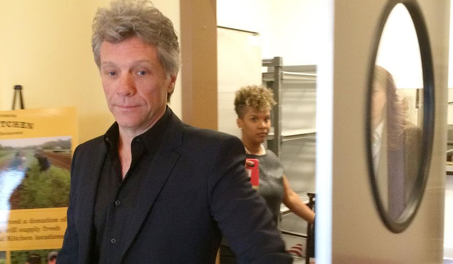 Musician and philanthropist Jon Bon Jovi emerges from the kitchen of a restaurant he established at a new anti-hunger center he and local charities opened, Tuesday, May 10, 2016 in Toms River, N.J., a community devastated by Superstorm Sandy and where many residents still need help. (AP Photo/Wayne Parry)