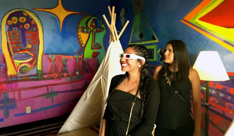 This May 5, 2016 photo Kalene Thompson, left, views an installation art piece by contemporary Native American artist Ishkoten Dougi through 3D glasses at the Nativo Lodge in Albuquerque, N.M. Nativo Lodge has transform 12 guest rooms in recent years into spaces that owners say can be considered art pieces unto themselves. (AP Photo/Mary Hudetz)