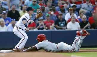 Philadelphia Phillies' Maikel Franco (7) is safe at third base on a Carlos Ruiz base hit as Atlanta Braves third baseman Gordan Beckham handles the late throw in the fourth inning of a baseball game, Tuesday, May 10, 2016, in Atlanta. (AP Photo/John Bazemore)
