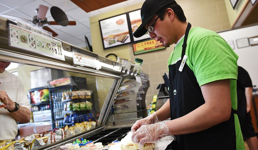 In this Tuesday, May 3, 2016 photo, Landon Honomicho, an employee at Subway, makes a sandwich for a customer, at the new Subway location at 85th Street and Louise Avenue in Sioux Falls, S.D. Honomicho has worked at the 85th Street and Louise Avenue Subway since it opened April 18. (Joe Ahlquist/The Argus Leader via AP) NO SALES; MANDATORY CREDIT