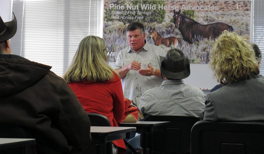 FILE- In this April 21, 2016, photo, Jim Havens, a board member of the Pine Nut Wild Horse Advocates, explains how he tracks mustangs to shoot them with a contraceptive dart during a presentation at the Fish Springs Fire Station in Gardnerville, Nev. Under the threat of another legal battle, the U.S. Bureau of Land Management has quietly pulled the plug on a public-private partnership in northern Nevada aimed at shrinking the size of a wild horse herd through the use of contraceptives, according to documents The Associated Press obtained on Tuesday, May 10. (AP Photo/Scott Sonner, File)