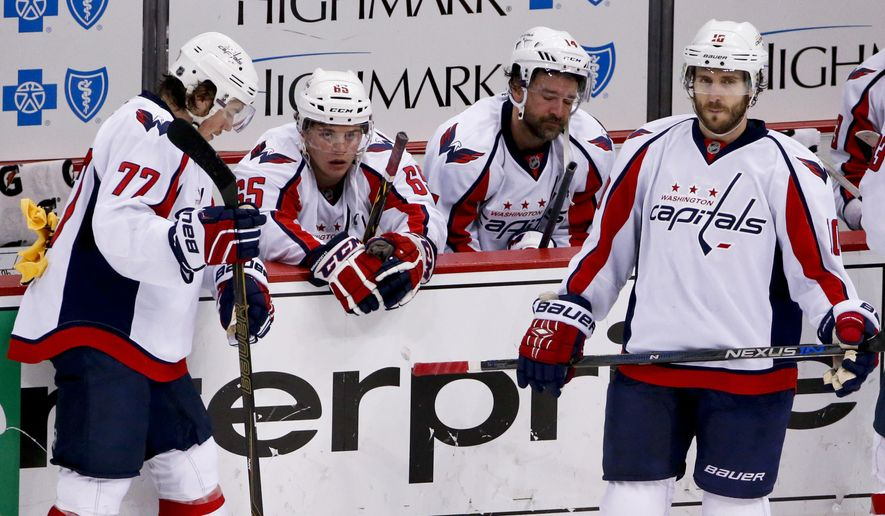 Washington Capitals' T.J. Oshie (77), Andre Burakovsky (65), Justin Williams (14) and Mike Richards (10) gather at their bench after the Capitals lost to the Pittsburgh Penguins in overtime of Game 6 of the NHL hockey Stanley Cup Eastern Conference semifinals, Tuesday, May 10, 2016 in Pittsburgh. The Penguins won 4-3 and advanced to the next round. (AP Photo/Gene J. Puskar)