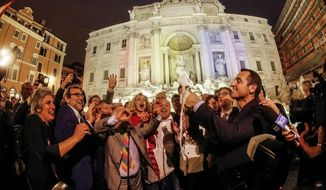 Gay rights activists celebrate in front of Rome's historical Trevi fountain after the lower Chamber approved a legislation granting same-sex couples many of the same rights as married couples, Wednesday, May 11, 2016. (Giuseppe Lami/ANSA via AP)